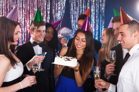 Beautiful young woman celebrating birthday with friends at nightclub