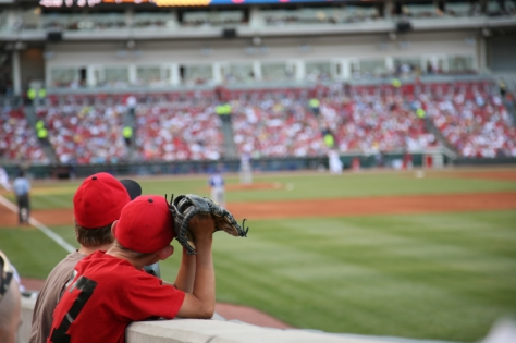 Two young boys hoping to catch a fly ball at a Cincinnati Reds baseball game