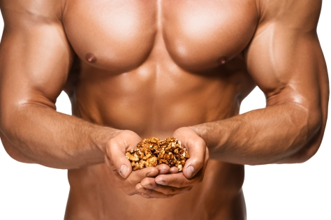 Shaped and healthy body man holding a walnuts, isolated on white background
