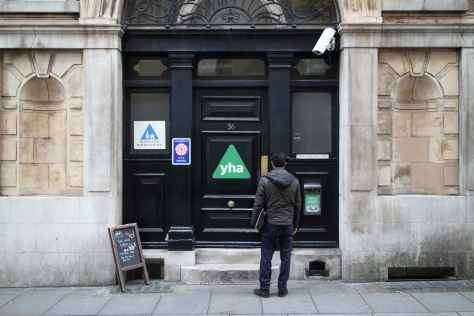 London, United Kingdom - March 17, 2015: A man at the entrance of the St Pauls Youth Hostel in London, England. The Youth Hostel Association provides accommodation in 200 locations in England and Wales