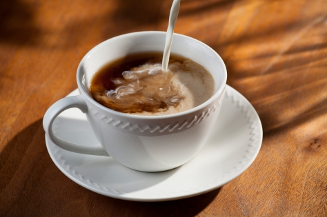 horizontal photograph of a cup of coffee with creamer being poured into it