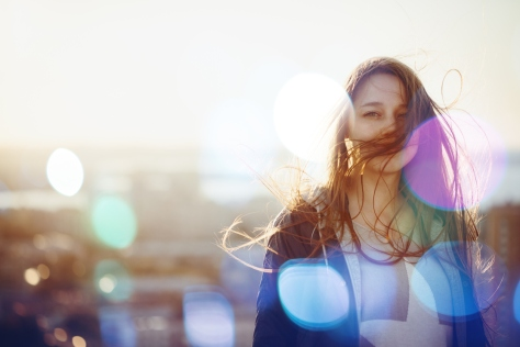Young Woman Standing in Sunset Light, Looking at Camera. Hair Fluttering in the Windi. Selective Focus, Bokeh Lights.