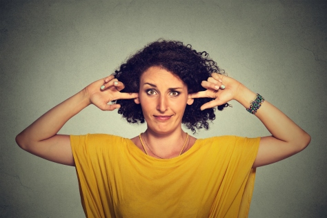 Annoyed woman plugging ears with fingers doesn't want to listen