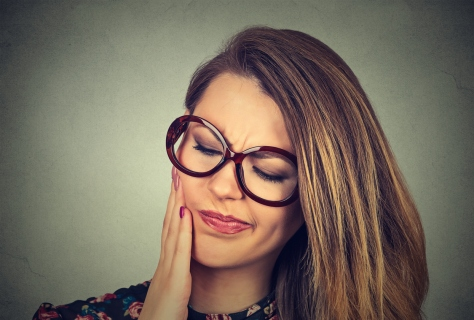 woman in glasses with sensitive toothache pain